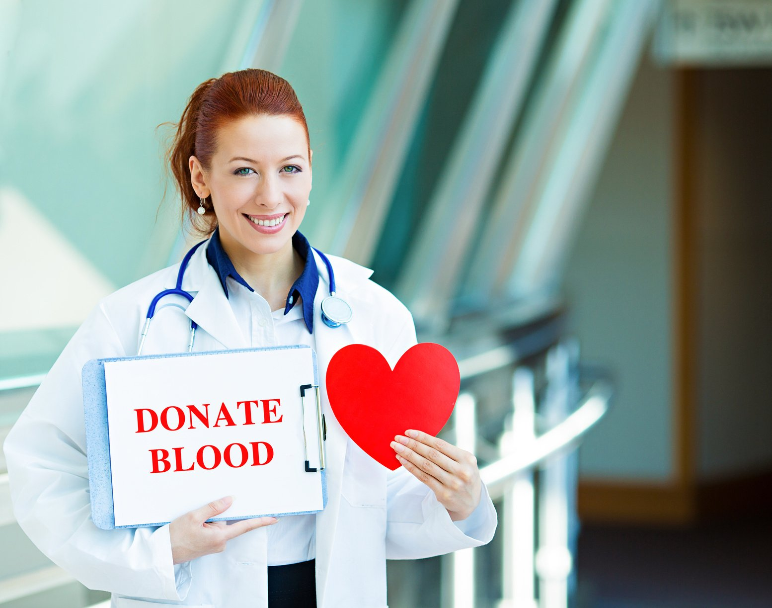 Closeup portrait happy smiling female health care professional woman doctor, transfusion medicine specialist holding sign donate blood, red heart isolated hospital hallway background. Patient plan